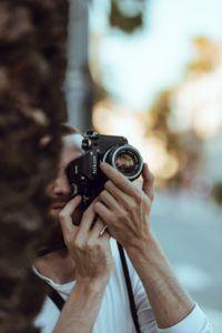 Person Using Black Nikon DSLR Camera
