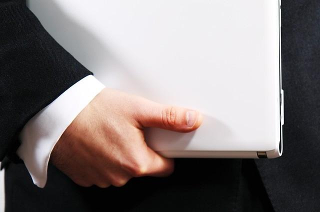 Man Holding a Laptop to Discuss Project Management Questions