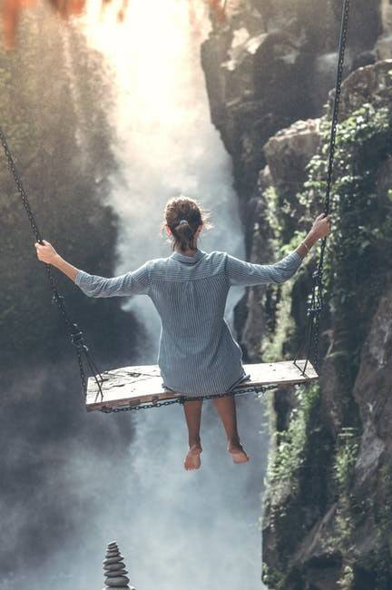 Woman Swinging Over a Waterfall
